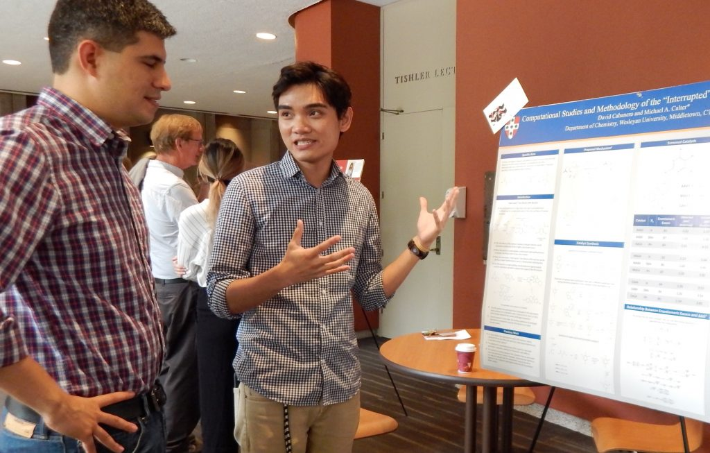 Image of Professor Carlos Jimenez-Hoyos and David Cabanero '19 standing in front of a poster discussing the project