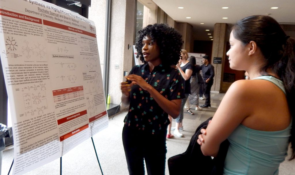 Image of Rochelle Spencer '20 discussing her poster with Giselle Reyes (Grad)